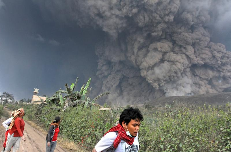 Villagers and a journalist prepare to flee as Mount Sinabung releases pyroclastic flows during an eruption in Namantaran, North Sumatra, Indonesia, Saturday, Feb. 1, 2014. The rumbling volcano in western Indonesia has unleashed fresh clouds of searing gas, killing a number people and injuring fewothers. (AP Photo)