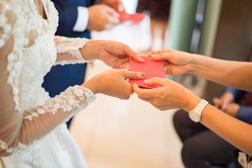 Elders giving red packet to newlywed couple