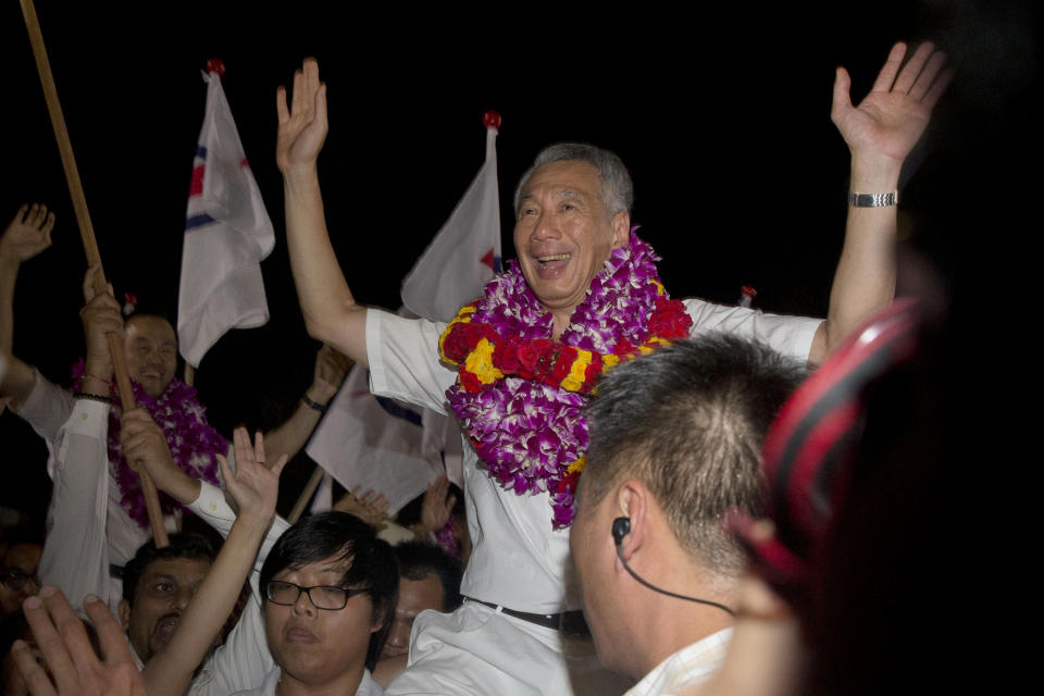 FILE - In this Sept. 12, 2015 file photo, Singapore's Prime Minister Lee Hsien Loong of the ruling People's Action Party (PAP) celebrates a win in his constituency in Singapore. Every four or five years Singaporeans vote in general elections without ever asking the question which party can best run the government. That's a no-brainer: It's the same party that's been ruling the wealthy Southeast Asian city-state for half-century. (AP Photo/Ng Han Guan, File)