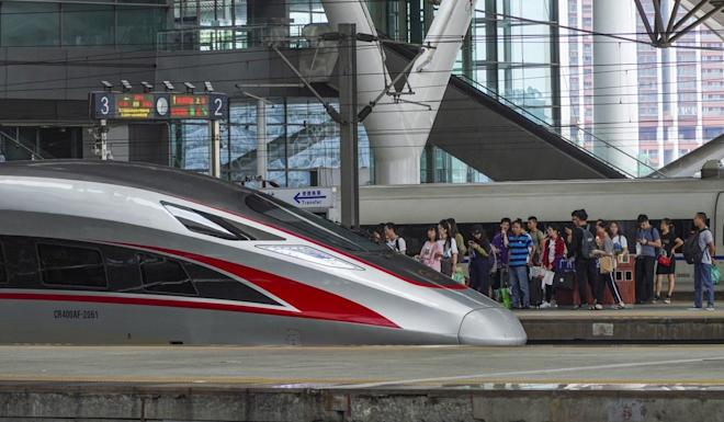 Travellers queue up to board a high-speed train at the Guangzhou South station. Photo: SCMP