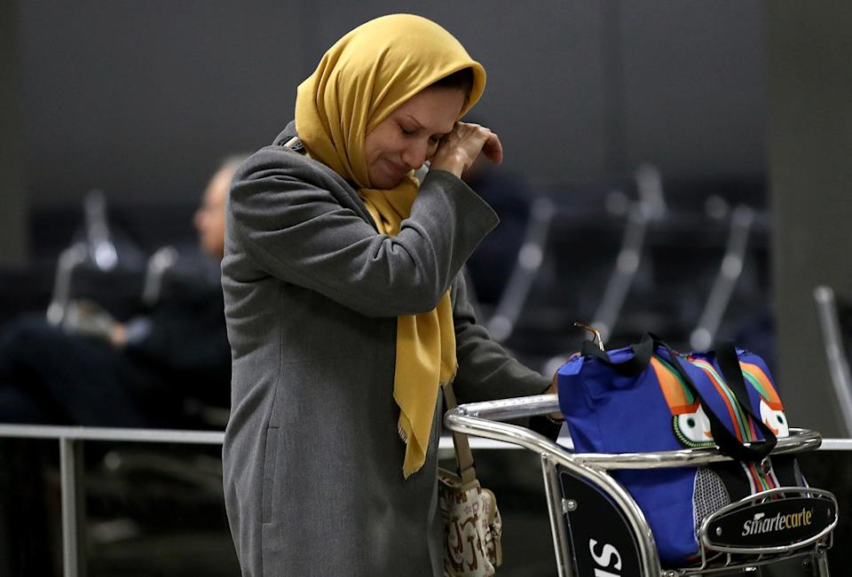 A woman traveling on a flight from Addis Ababa, Ethiopia, wipes away a tear after greeting a relative at Dulles International Airport on Feb. 6, 2017.
