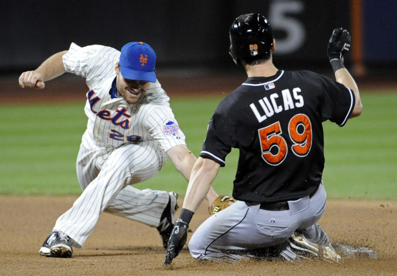 Miami Marlins' Ed Lucas (59) is safe at second base with a double as New York Mets second baseman Daniel Murphy applies a late tag during the fifth inning of a baseball game on Friday, Sept. 13, 2013, in New York. (AP Photo/Bill Kostroun)