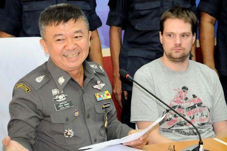 Hans Fredrik Lennart Neij (R), a co-founder of the Swedish file-sharing website, The Pirate Bay, is surrounded by police officers at the immigration office in Nong Khai province November 4, 2014. REUTERS/ Daily News