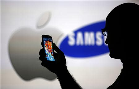 A man is silhouetted against a video screen with Apple and Samsung logos as he poses with a Samsung Galaxy S4 in this photo illustration taken in the central Bosnian town of Zenica, in this August 14, 2013, file photo. REUTERS/Dado Ruvic/Files