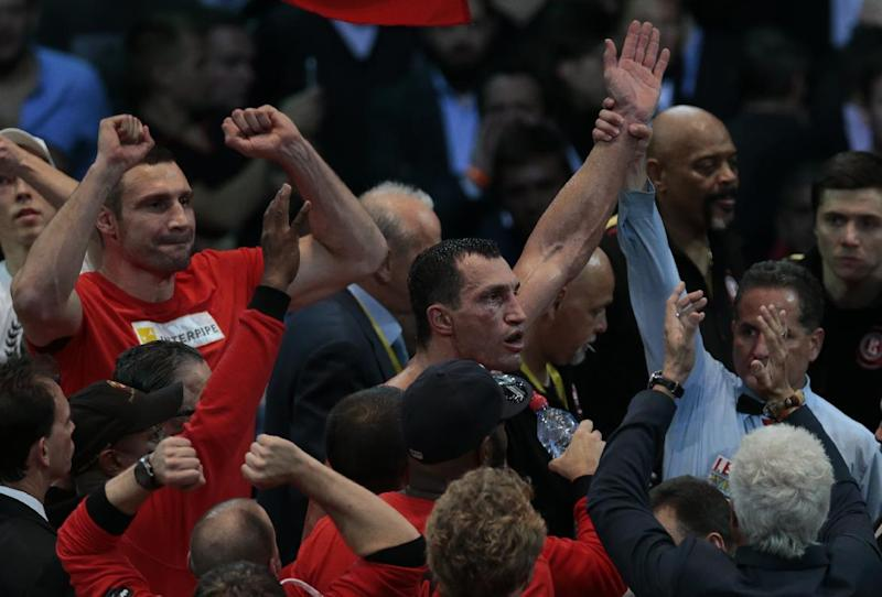 Heavyweight champion Wladimir Klitschko, of Ukraine, center, reacts after a bout with Alexander Povetkin, of Russia, unseen, at the Olympic Stadium, in Moscow, Russia, on Saturday, Oct. 5, 2013. Wladimir Klitschko successfully defended his WBA and IBF titles. (AP Photo/Ivan Sekretarev)