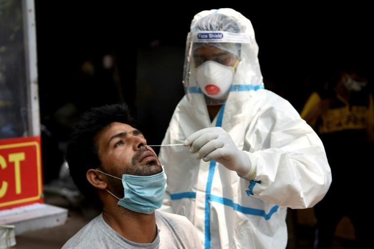 A health official collects a swab sample from a man to test for coronavirus in New Delhi on August 8, 2020