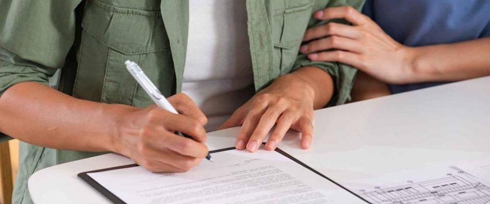 Close up of one woman holding another woman's arm as she signs a contract.