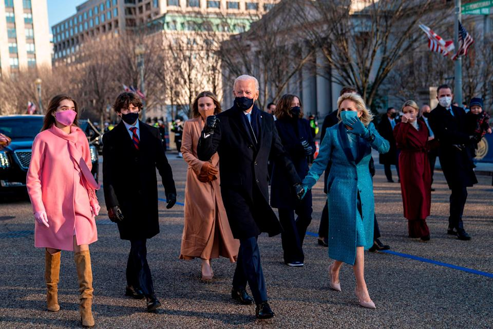 President Joe Biden and first lady Jill Biden walk along Pennsylvania Avenue in front of the White House during Inaugural celebrations, on January 20, 2021, with family members after Biden was sworn in as the 46th president of the United States.