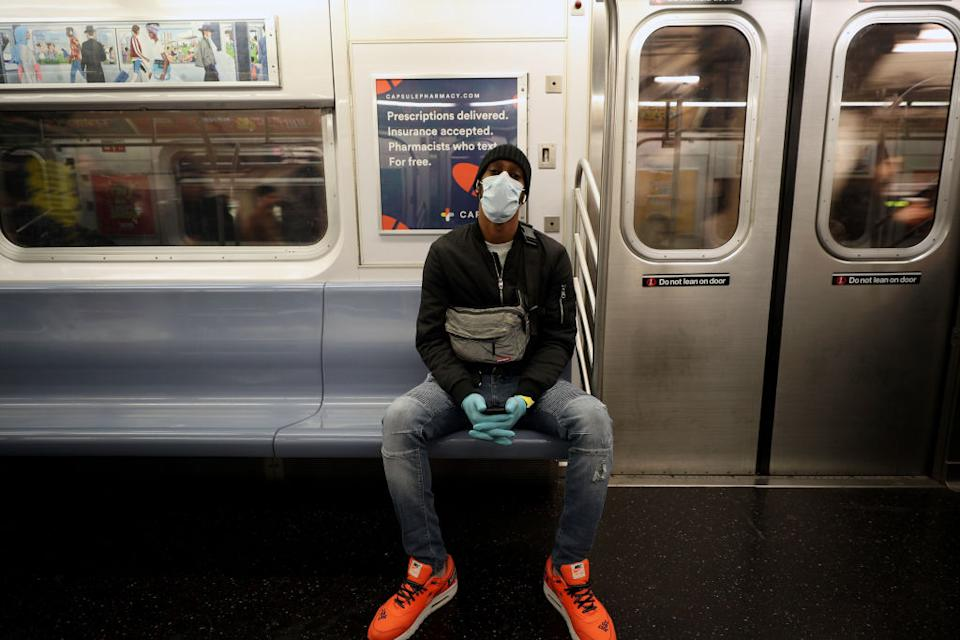 A man wears a face mask and surgical gloves to prevent Covid-19 spread on a New York City subway train. Source:  AP