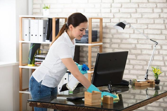 Woman Cleaning The Glass Office Desk With Rag
