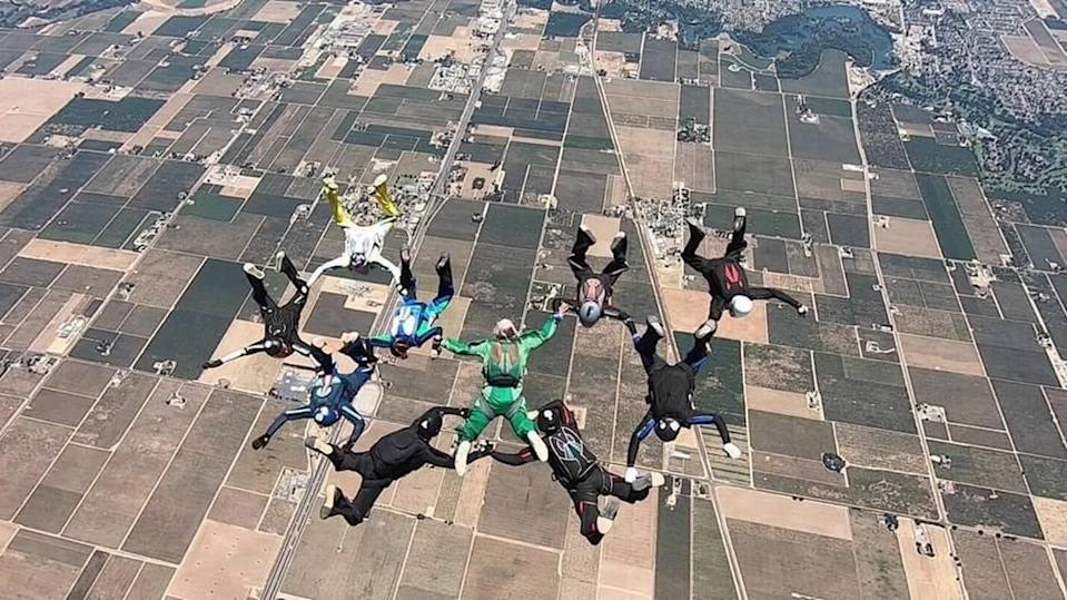 "Sabrina Call, in the teal and green suit, links arms with her husband, Mark ""Shoobie"" Knutson, in green, during a group skydive. Call was an avid skydiver with more than 2,100 jumps to her name."