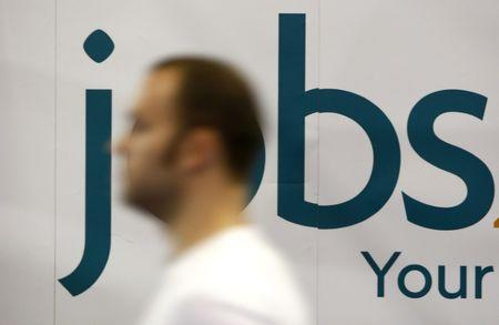 A man passes a trade exhibition stand at the Careers and Jobs Live careers fair at the ExCeL centre in London