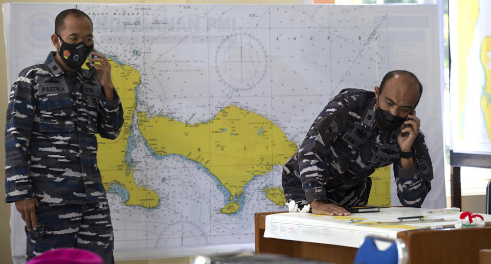 Indonesian military officials speak on the phone in front of a map of the location where the Indonesian Navy submarine KRI Nanggala that went missing while participating in a training exercise on Wednesday.