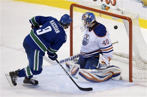 Vancouver Canucks' Zack Kassian scores a goal against Edmonton Oilers goalie Devan Dubnyk during the second period of an NHL hockey game in Vancouver, British Columbia, on Sunday, Jan. 20, 2013. (AP Photo/The Canadian Press, Darryl Dyck)