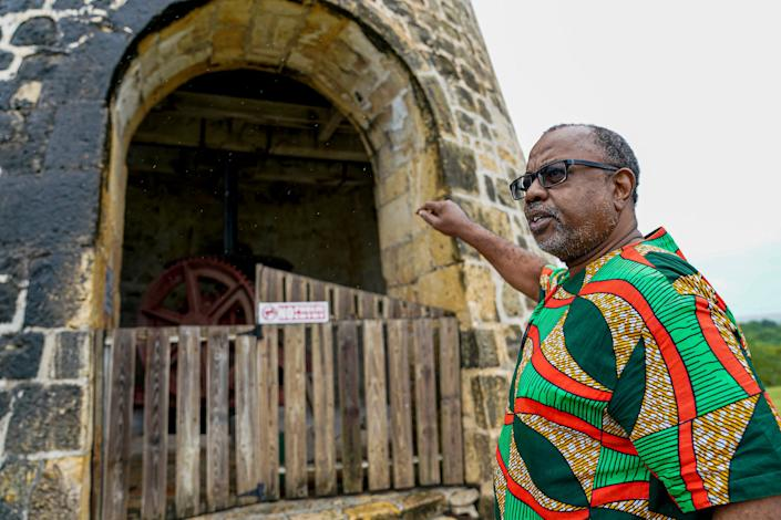 Dorbrene O'Marde, chairman of the Antigua and Barbuda Reparations Commission, talks about how sugar mills were once key to the country's economy during a visit to Betty's Hope, a former plantation.