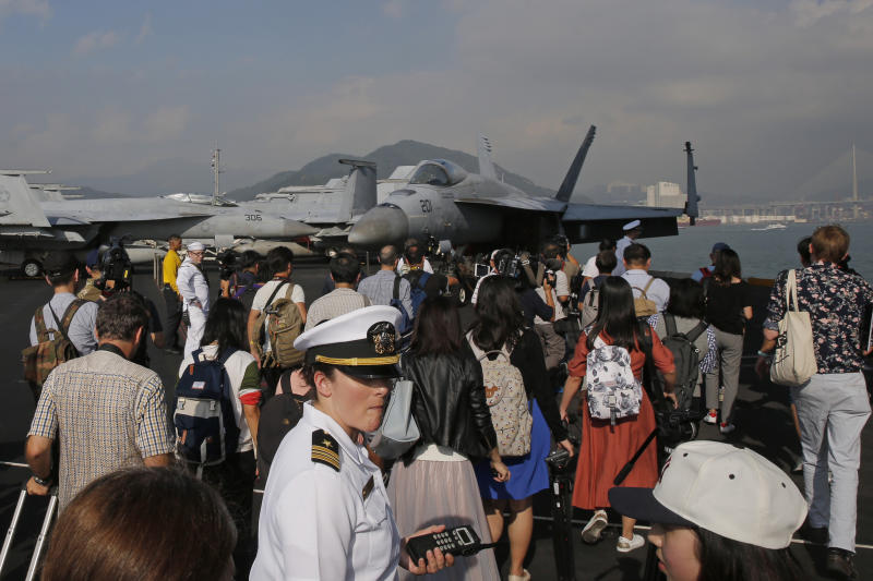 Journalists and navy sailors gather on the deck of the U.S. Navy USS Ronald Reagan aircraft carrier in Hong Kong, Wednesday, Nov. 21, 2018. The USS Reagan docked in Hong Kong on Wednesday, days after a pair of American B-52 bombers flew over the disputed South China Sea. (AP Photo/Kin Cheung)