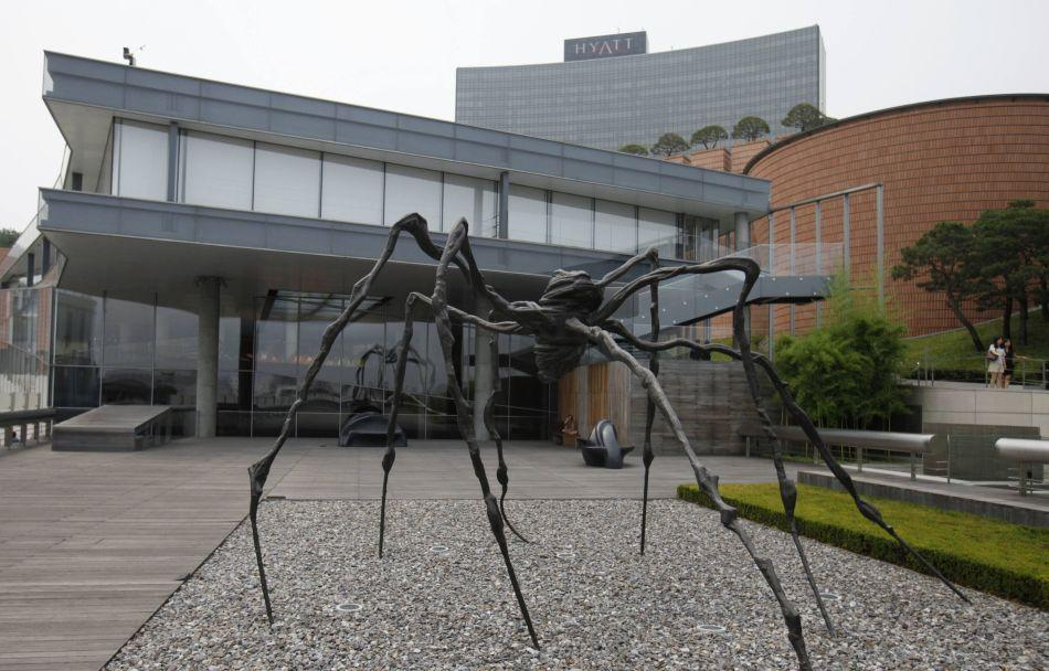 People walk past a spider sculpture by artist Louise Bourgeois at the Leeum Gallery in Seoul. Run by the Samsung Foundation of Culture, the museum consists of two sections that house Korean and contemporary art.