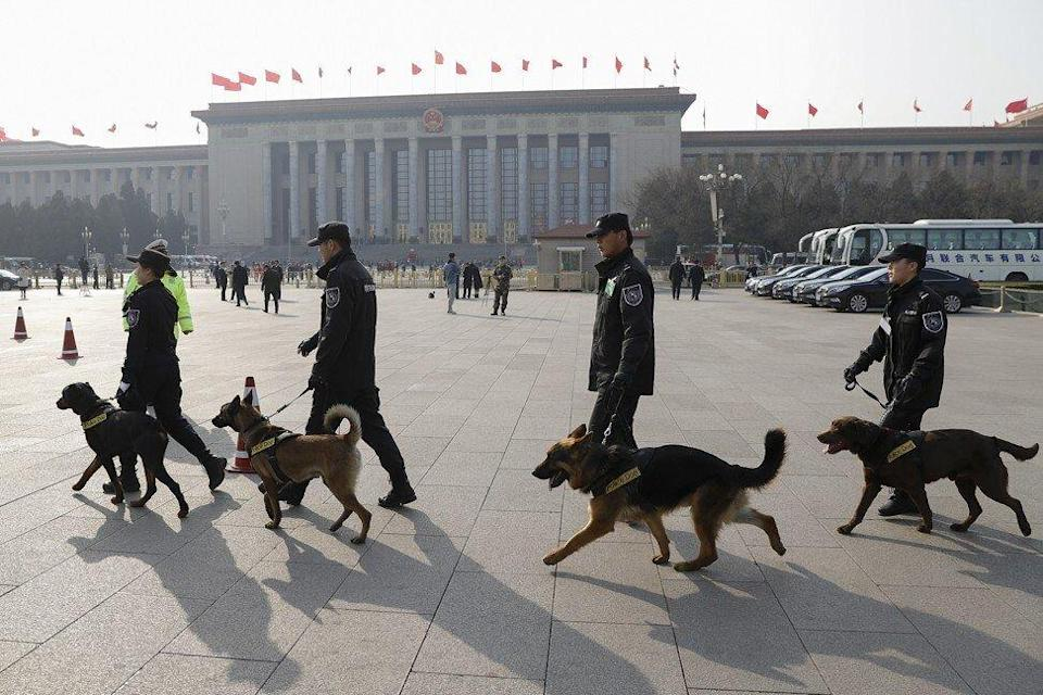 Police officers and dogs patrol outside the Great Hall of the People in Beijing, China. Photo: Getty