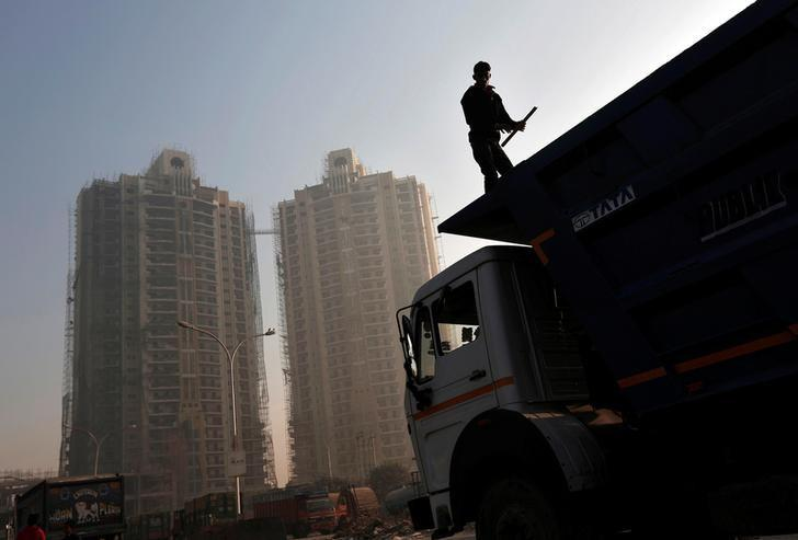 A labourer stands on a truck carrying construction materials at a construction site of residential buildings in Noida