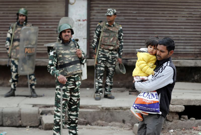 A man carrying a child walks past security forces in a riot affected area following clashes between people demonstrating for and against a new citizenship law in New Delhi