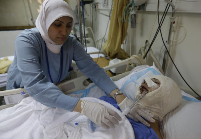A Lebanese nurse treats an injured man who was seriously wounded by a car explosion in the southern suburb of Beirut, Lebanon, Friday, Aug. 16, 2013. A powerful car bomb tore through a bustling south Beirut neighborhood that is a stronghold of Hezbollah on Thursday, killing at least 18 and trapping dozens of others in an inferno of burning cars and buildings in the bloodiest attack yet on Lebanese civilians linked to Syria's civil war. (AP Photo/Hussein Malla)