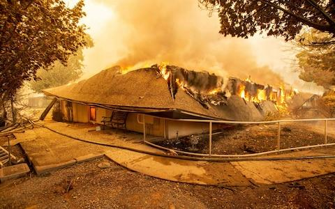The Feather River Hospital burns down during the Camp fire in Paradise - Credit: AFP