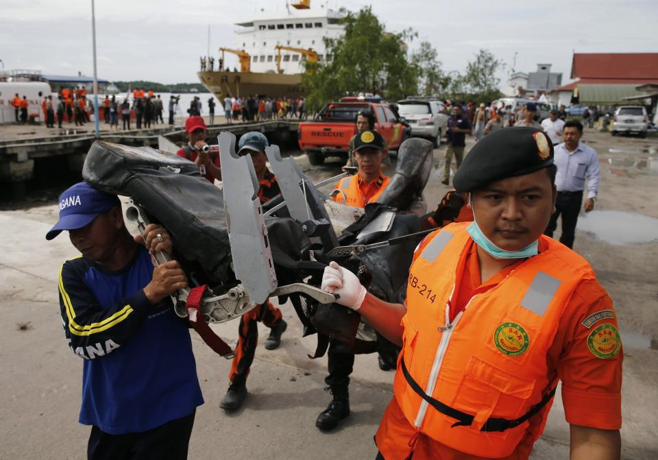 Rescue team members walk as they carry the wreckage of a seat of the AirAsia Flight QZ8501 airliner at Kumai port in Pangkalan Bun, January 19, 2015. The flight lost contact with air traffic control in bad weather on December 28, less than halfway into a two-hour flight from the Indonesian city of Surabaya to Singapore. REUTERS/Beawiharta (INDONESIA - Tags: DISASTER TRANSPORT TPX IMAGES OF THE DAY)