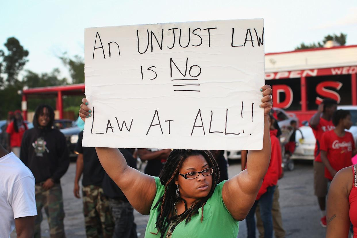 FERGUSON, MO - AUGUST 11: Demonstrators protest the killing of 18-year-old Michael Brown who was shot by police on Saturday on August 11, 2014 in Ferguson, Missouri. Police responded with tear gas and rubber bullets as residents and their supporters protested the shooting by police of an unarmed black teenager named Michael Brown who was killed Saturday in this suburban St. Louis community. Yesterday 32 arrests were made after protests turned into rioting and looting in Ferguson. (Photo by Scott Olson/Getty Images)