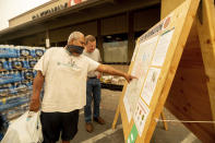 As new evacuation orders take effect for the Dixie Fire, Carlos Duran, left, and Rich McFeely examine a fire map in Quincy, Calif., on Sunday, July 25, 2021. (AP Photo/Noah Berger)