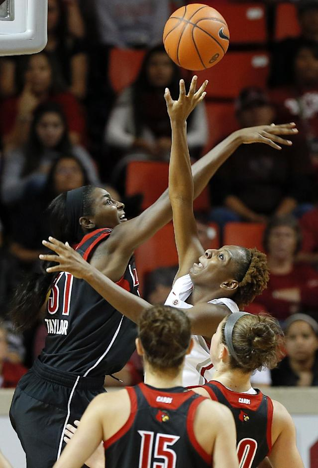 Oklahoma's Sharane Campbell, right, tries to get past Louisville's Asia Taylor during the first half of an NCAA college basketball game in Norman, Okla., Sunday, Nov. 17, 2013. (AP Photo/Bryan Terry)