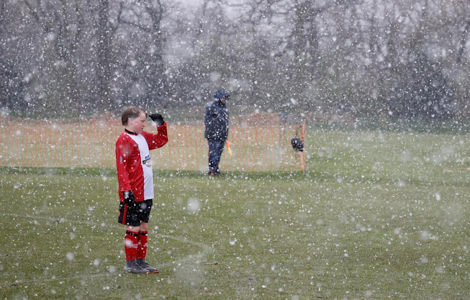 A young footballer shields his eyes during an unexpected snow storm in Altrincham, UK, on 10 April, 2021.  (REUTERS)