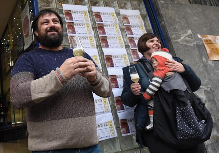 """Spanish national lottery shop owner and lottery winner David Lobato (L) celebrates the sale of 50 first prize tickets in the Christmas lottery, """"El Gordo"""", in the Basque village of Abadino on December 22, 2016 (AFP Photo/ANDER GILLENEA)"""