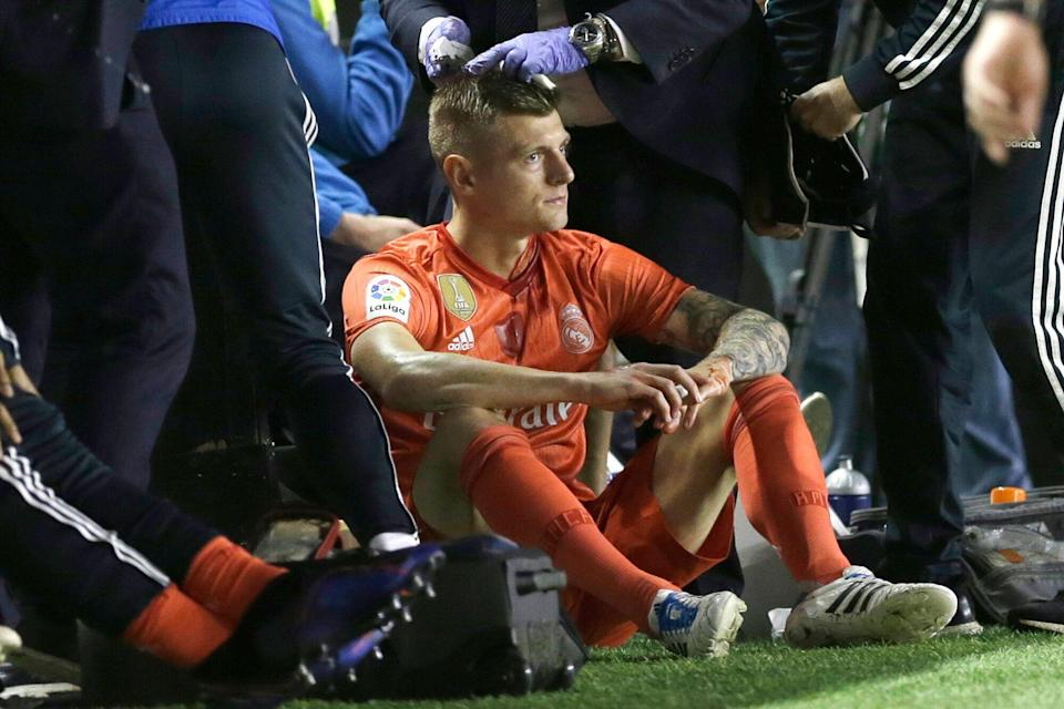 Real Madrid's Toni Kroos is treated for a bleeding head during a Spanish La Liga soccer match between Rayo Vallecano and Real Madrid at the Vallecas stadium in Madrid, Spain, Sunday, April 28, 2019. (AP Photo/Paul White)