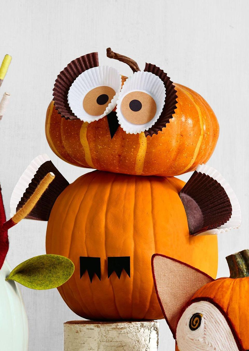 <p><em>H00</em> could resist crafting this stacked owl? <br><strong><br>Make the pumpkin:</strong> For the face, cut two circles (around the same circumference as a cupcake liner) on light brown paper and glue them to the bottom of two white liners. Cut out or draw two smaller black dots for the pupils. As for the lashes, cut a brown cupcake liner in half. Hot glue the eyes to the pumpkin.</p><p>For wings, cut a brown and a white liner in half and attach to the sides of bottom pumpkin. Cut a triangle beak and feet from black card stock and glue to the body. </p>