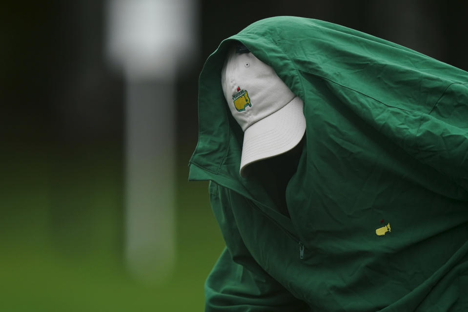 Joe Mulholland puts on a rain jacket during a practice round at the Masters golf tournament Wednesday, Nov. 11, 2020, in Augusta, Ga. (AP Photo/David J. Phillip)