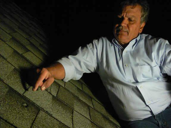 The dent in a roof caused by a meteorite from the Oct. 17, 2012, fireball over Northern California is identified by Luis Rivera, the neighbor of Lisa Webber who found the meteorite after it struck her Novata, Calif., home.