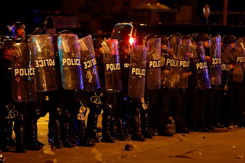 Police stand guard during disturbances following the police shooting of a man in Milwaukee in early August. (Photo: Aaron P. Bernstein/Reuters)