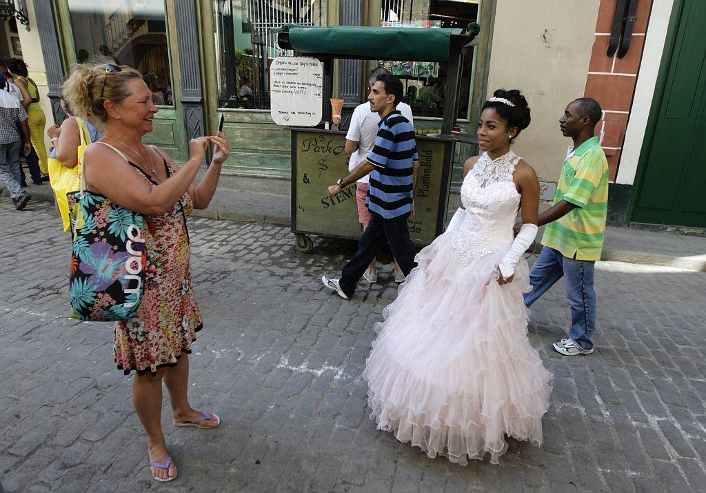 <p>A tourist photographs Carmen Gonzalez (R), who is dressed for a photo session, in the old quarters of Havana as part of her quinceanera.</p>