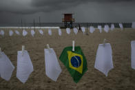 """A Brazilian flag hangs on a clothesline on Copacabana beach amid white scarves that represent those who have died of COVID-19 in Rio de Janeiro, Brazil, Friday, Oct. 8, 2021. The action was organized by the NGO """"Rio de Paz"""" to protest the government's handling of the pandemic as the country nears a total of 600,000 COVID-19 related deaths. (AP Photo/Bruna Prado)"""