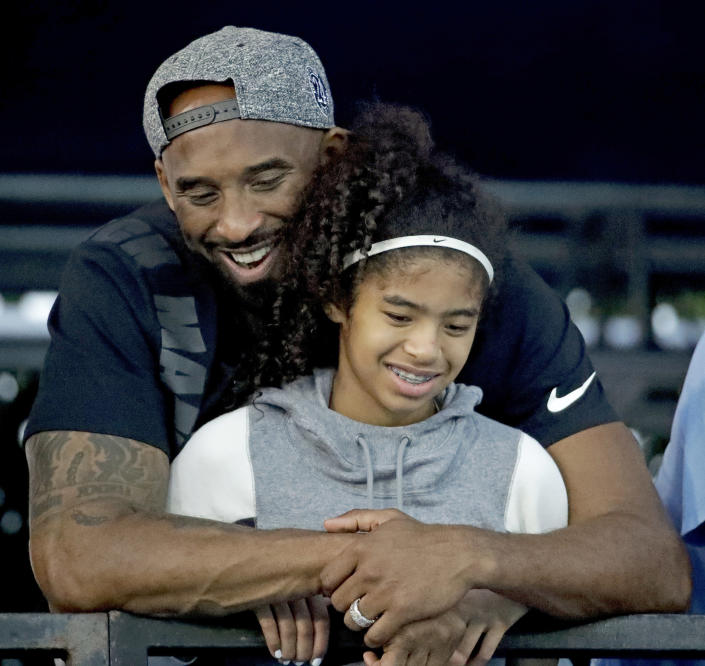 FILE - In this July 26, 2018, file photo, former Los Angeles Laker Kobe Bryant and his daughter Gianna watch during the U.S. national championships swimming meet in Irvine, Calif. Autopsy reports released Friday, May 15, 2020, show that the pilot who flew Bryant did not have drugs or alcohol in his system when the helicopter crashed in Southern California in January, killing all nine aboard. The causes of death for Bryant, his 13-year-old daughter Gianna, pilot Ara Zobayan and the others have been ruled blunt force trauma. Federal authorities are still investigating the crash. (AP Photo/Chris Carlson, File)