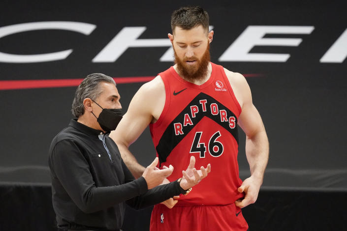 Toronto Raptors assistant coach Sergio Scariolo talks to center Aron Baynes (46) during the first half of an NBA basketball game against the Houston Rockets Friday, Feb. 26, 2021, in Tampa, Fla. Scariolo is filling in for head coach Nick Nurse, who is under coronavirus protocol. (AP Photo/Chris O'Meara)