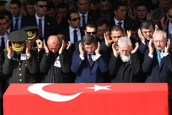 Turkish Prime Minister Ahmet Davutoglu (C), Chief of Staff General Hulusi Akar (L), main opposition Republican People's Party leader Kemal Kilicdaroglu (R) and family members pray behind the Turkish flag-draped coffin of a car bombing victims (AFP Photo/Adem Altan)