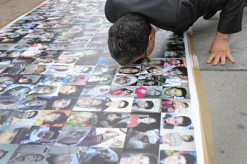 HNC spokesman Salem al-Meslet kisses a banner showing pictures of children killed during the Syrian war, outside of the United Nations offices on February 2, 2016 in Geneva (AFP Photo/Fabrice Coffrini)
