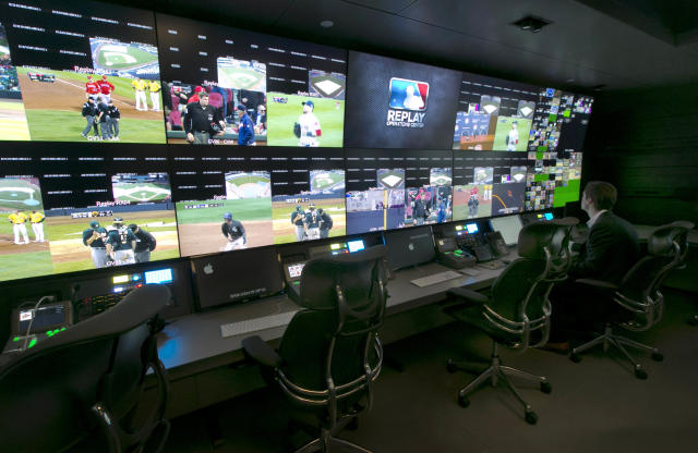 A technician works in front of a bank of television screens during a preview of Major League Baseball's Replay Operations Center, in New York, Wednesday, March 26, 2014. Less than a week before most teams open, MLB is working on the unveiling of its new instant replay system, which it hopes will vastly reduce incorrect calls by umpires. (AP Photo/Richard Drew)