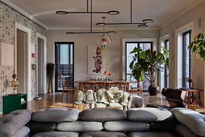 """<div class=""""caption""""> The dining area is outfitted with a Hans Wegner dining table and chairs, a photographic work by Adam Fuss, candlesticks by Ted Muehling, and a Bec Brittain pendant lamp from Matter. </div>"""