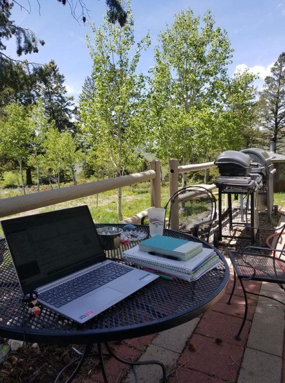 laptop on table with books outside