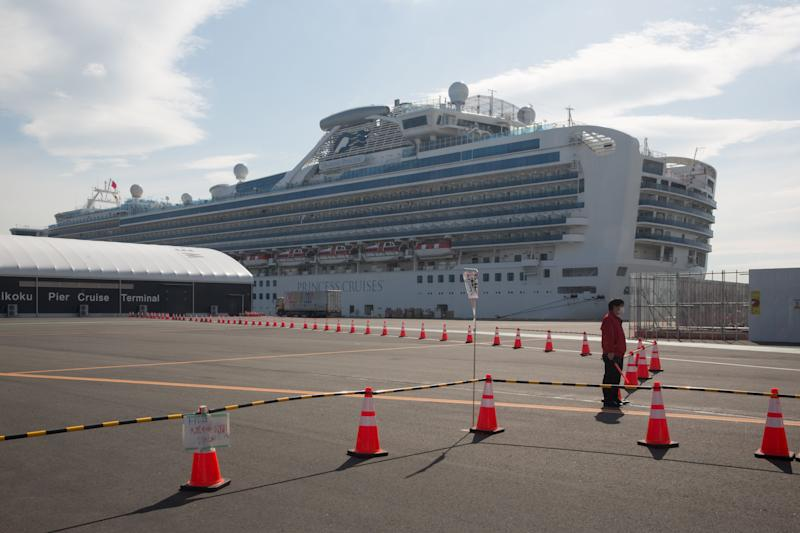 A guard stands at a restricted area in front of the Diamond Princess cruise ship in Yokohama (Photo: SIPA USA/PA Images)