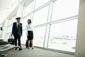 Pilot and flight attendant with luggage talking and walking to gate at airport