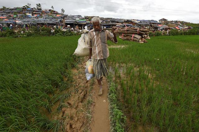 <p>A Rohingya refugees carry supplies in the refugee camp of Thyangkhali near the Bangladeshi village of Gumdhum, on Sept. 18, 2017. (Photo: Dominique Faget/AFP/Getty Images) </p>