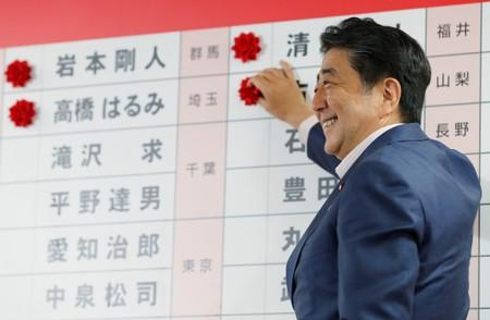 Japan's Prime Minister Shinzo Abe, who is also leader of the ruling Liberal Democratic Party (LDP), puts a rosette on the name of a candidate who is expected to win the upper house election, at the LDP headquarters in Tokyo
